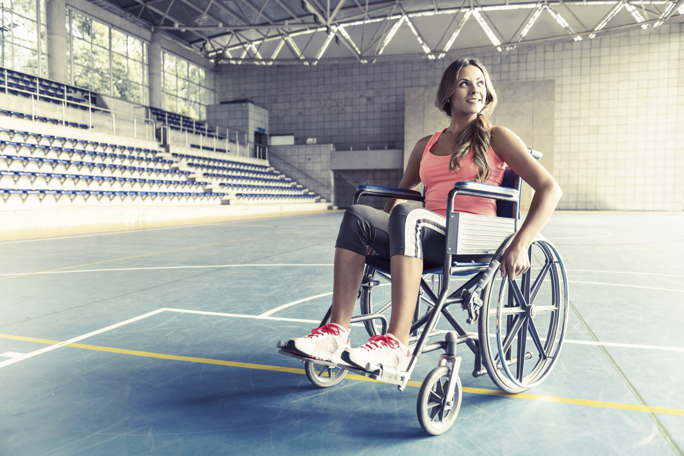 Injured sports woman in a wheelchair at a basketball court